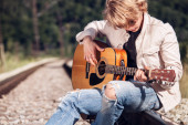 Man playing on guitar on the railway — Stock Photo
