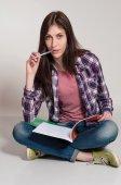 Young woman (teen girl) reading book. Grey background — Stok fotoğraf