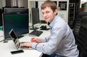 Young handsome happy man with computer in the office. Programmin — Stock Photo
