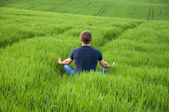 Man sits in the middle of a green meadow — Stock Photo