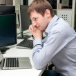 Young handsome man with computer in the office. Thinking over ta — Stock Photo #75273193