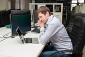 Young handsome man with computer in the office. Thinking over ta — Stock Photo