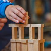 Hand putting Wood Building Block on a Constuction — Stock Photo