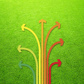 Sunny artificial green grass with arrows — Stock Photo