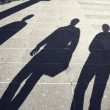 Busy people shadows on paved city street — Stock Photo #74336273