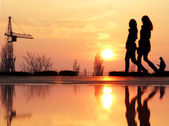 Silhouette of two friends with sunset on a background. Couple of young women best friends walking during sunset - Teenager girls having fun together outdoors — Stock Photo
