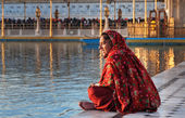Woman in a red saree sits and pray in Golden Temple in the early morning. Amritsar. India — Stock Photo