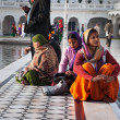 Indian women sitting near the lake at Golden Temple. Amritsar. India — Stock Photo #64651531