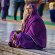 Indian women in purple sari sitting near the lake at Golden Temple. Amritsar. India — Stock Photo #64651603