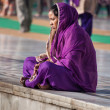 Indian women in purple sari sitting near the lake at Golden Temple. Amritsar. India — Stock Photo #64651615