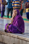 Indian women in purple sari sitting near the lake at Golden Temple. Amritsar. India — Stock Photo