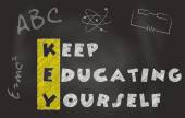Acronym Of Key Over Black Chalkboard. Keep Educating Yourself Slogan — Stock Photo