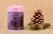 Pine cone and candle on sackcloth background — Stockfoto