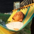 Young man relaxing hanging chair — Stock Photo #76557897