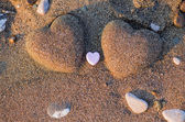 Two sand heart shape in the sand by the sea — Stock Photo