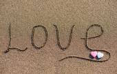 """Word """"love"""" on sand background — Stock Photo"""