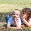 Little boy and the girl lie together on a grass — Stock Photo #66340355