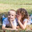Little boy and the girl lie together on a grass — Stock Photo #66340387