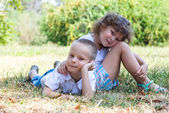 Little boy and the girl lie together on a grass — Stock Photo