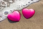 Two red hearts on the beach symbolizing love — Stock Photo