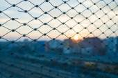Blurred cityscape beyond metal fence — Stock Photo