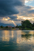 Cloudscape and sunbeams on lake — Stock Photo