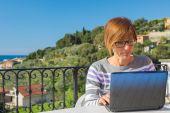 Женщина, работающая с netbook на открытом воздухе — Стоковое фото