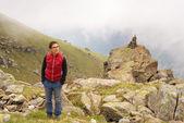 Woman standing on the mountain summit — Stock Photo