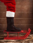 Red sled with the boot of Santa Claus — Стоковое фото