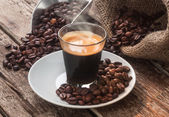 Espresso coffee in glass cup with coffee beans. — Stock Photo