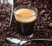 Espresso coffee in glass cup with coffee beans. — ストック写真