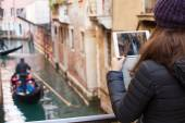 Young girl using a tablet to take pictures of gondolas of Venice — Stock Photo