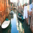 Venetian canal with boats and clothes hanging out to dry — Stock Photo #64394525