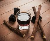 Licorice liqueur with pure blocks and roots. — Stock Photo