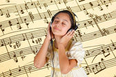 Young girl in ancient dress while listening music with headphone — Stock Photo