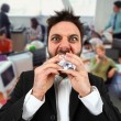 Angry businessman while eating balled paper in office. — Stock Photo #71255747