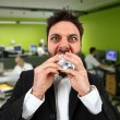 Angry businessman while eating balled paper in office. — Stock Photo #71255753