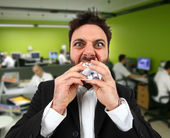Angry businessman while eating balled paper in office. — Stock Photo