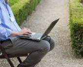 Unternehmer einen Laptop auf den Knien holding — Stockfoto