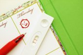 Pregnancy test with a positive result and female diary. — Stock Photo