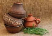Pottery and dill on a background of burlap. — Stock Photo