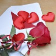 The envelope with the card and hearts, red rose with decorative ribbon is on the table. The view from the top — Stock Photo #63835687