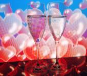 Two glasses of champagne on the background of hearts with the reflection on the table — Stock Photo