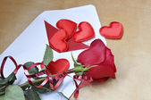 The envelope with the card and hearts, red rose with decorative ribbon is on the table. The view from the top — Stock Photo