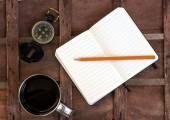 Cup of coffee with compass and notepad — Stock Photo