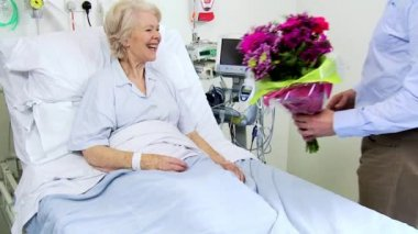 Senior Patient Being Visited by Son With Flowers — Stock Video