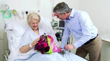 Caring Son Bringing Flowers Senior Mom Hospital Bed — Stock Video