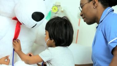 Child patient playing with stethoscope and teddy bear — Stock Video