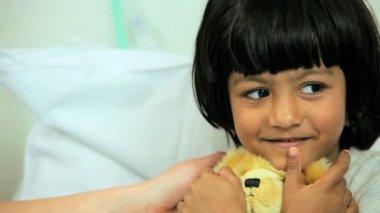 Niña abrazando oso de peluche en la cama de hospital — Vídeo de Stock