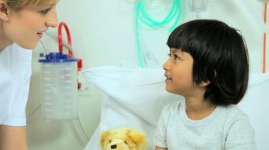 Girl clutching teddy bear in hospital bed — Stock Video